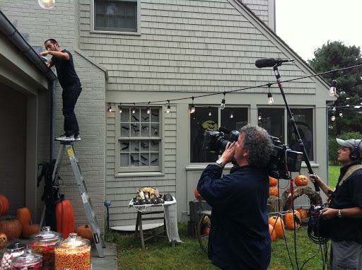 Javier has his moment on camera, decorating the eves of the Maple Avenue house.