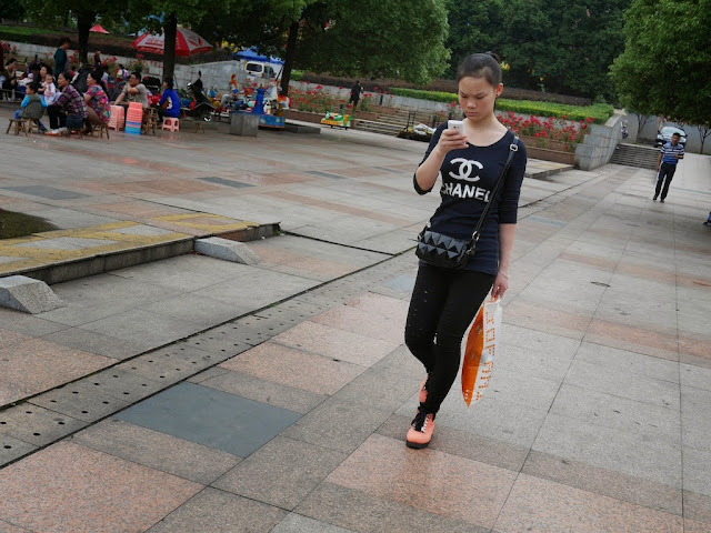 young woman in China wearing a possible knockoff Chanel shirt