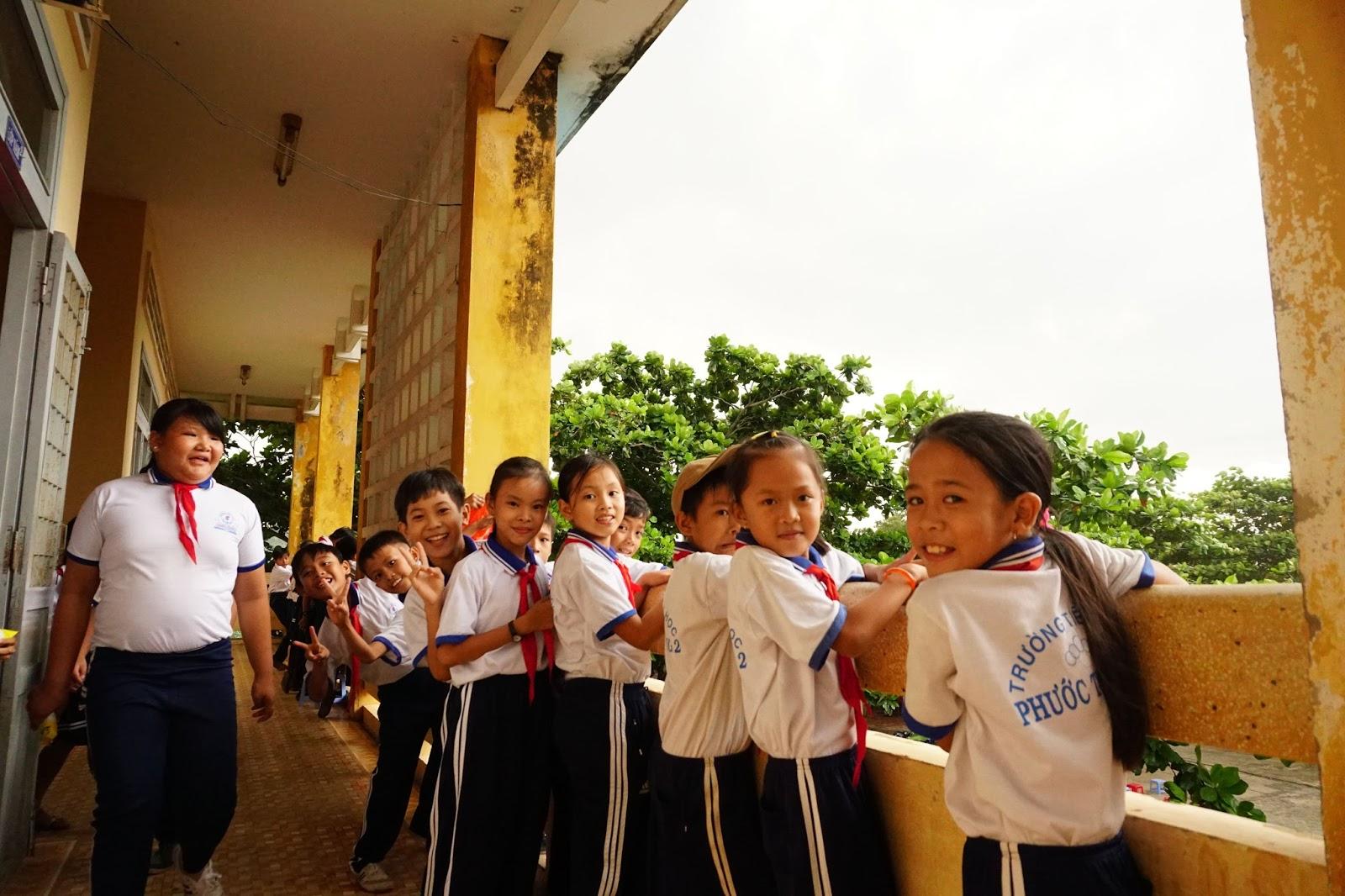 Các em học sinh ngồi hóng cho trời hết mưa nhanh để kịp nhận quà