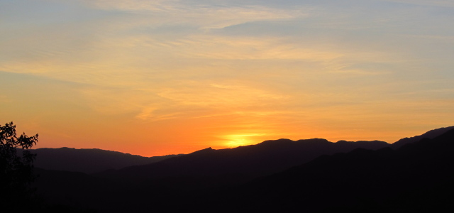 sun setting over the hills