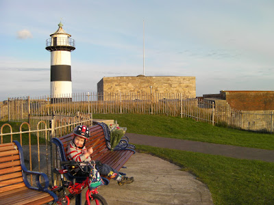 Henry 8th's Castle, portsmouth boy cyclist sitting on viewing bench by southsea bandstand