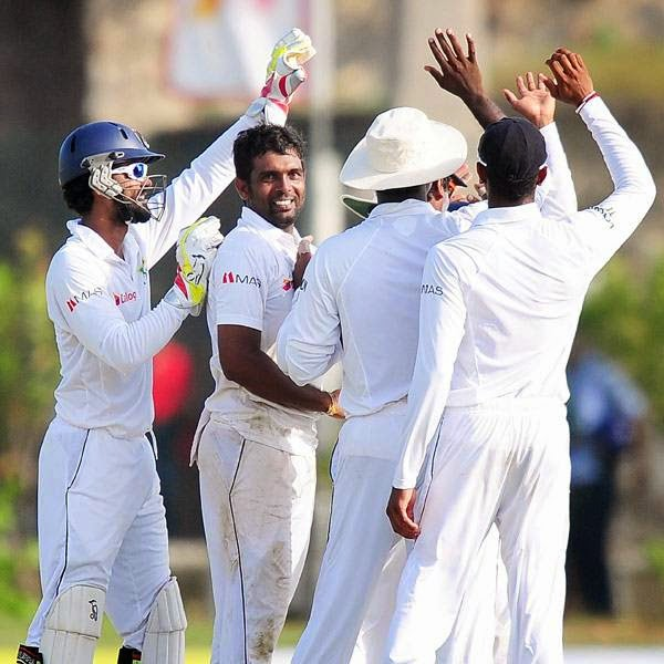 Sri Lankan bowler Dilruwan Perera (2L) celebrates with teammates after dismissing unseen South Africa cricketer Faf du Plessis during the first day of the opening Test match between Sri Lanka and South Africa at the Galle International Cricket Stadium in Galle on July 16, 2014.