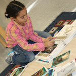 Elementary students learn to do research on areas that interest them, using many rich materials their teachers provide--like this girl, who is studying birds of prey as part of a unit on animals.