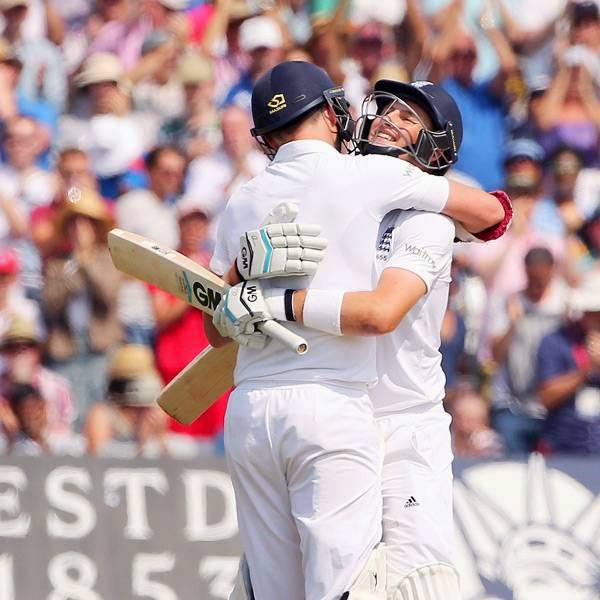 England's Joe Root (R) celebrates reaching 100 runs with England team mate James Anderson (L) during the fourth day of the first cricket Test match between England and India at Trent Bridge in Nottingham, central England, on July 12, 2014.