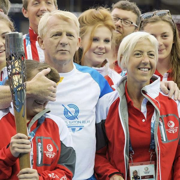 Gordon Strachan, manager of the Scottish National Football team, poses for pictures with 'games makers' as he carries the 2014 Commonwealth Games baton at Hampden Park Stadium in Glasgow, Scotland on July 22, 2014, ahead of the start of the 2014 Commonwealth Games which begin on July 23, 2014.