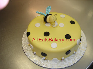 Custom designed yellow, black and white fondant baby shower cake with Mama and baby bee topper
