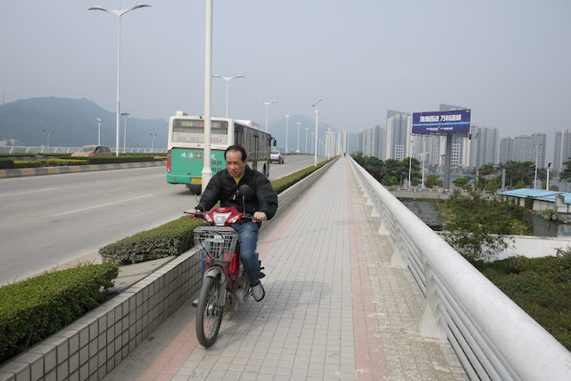 man riding a motorbike on a bridge in Zhuhai, China