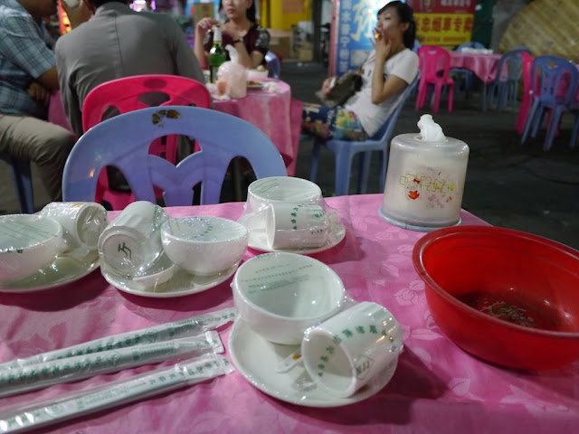 plastic wrapped table setting on an outdoor table with a young woman smoking in the background in Zhuhai, China
