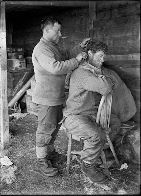 Anton Omelchenko cuts Patrick Keohane's hair at their camp in the Ross Dependency of Antarctica, during Captain Robert Falcon Scott's Terra Nova Expedition to the Antarctic, January 1912. (Photo by Herbert Ponting/Scott Polar Research Institute, University of Cambridge/Getty Images)
