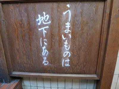 階段脇に書かれた「うまいものは地下にある」の文字