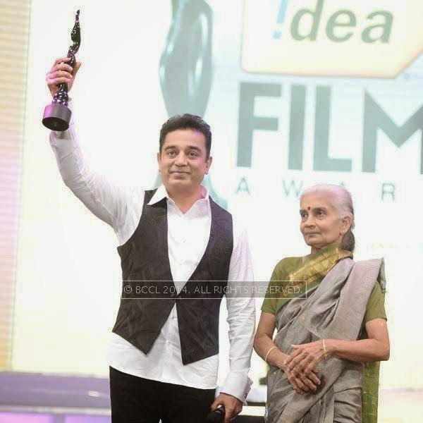 Kamal Haasan gestures as he presents the Lifetime Achievement Award to Balu Mahendra, which is received by his wife Akhila to a standing ovation by the crowd during the 61st Idea Filmfare Awards South, held in Chennai, on July 12, 2014.