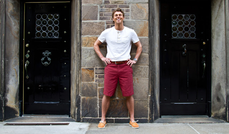 Red Bedford Shorts Lean against Stone wall in New York