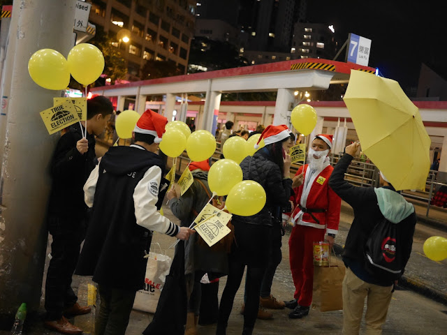 group dressed in Christmas spirit carrying various Umbrella Movement items