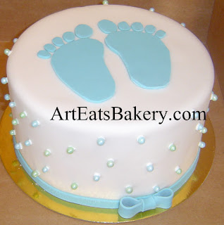 Unique white fondant baby shower cake with blue feet, edible sugar pearls and bow idea picture