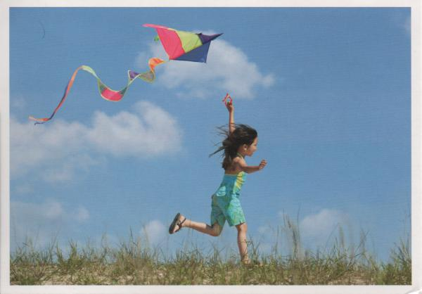 child flying a kite on sand dunes