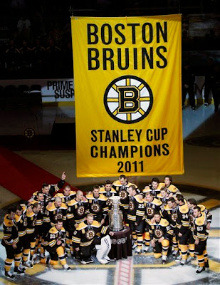 Boston Bruins pose with the Stanley Cup and championship banner