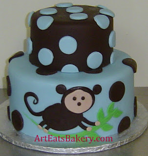 Two tier boys blue and brown baby shower cake with polka dots and monkey