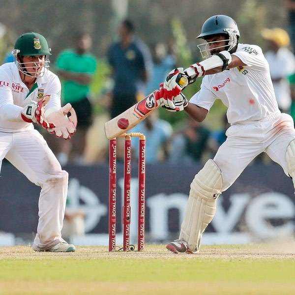 Sri Lankan batsman Kaushal Silva plays a shot, as South African wicketkeeper Quinton de Kock cups his hands to catch the ball during the fourth day of the first test cricket mach between Sri Lanka and South Africa in Galle, Sri Lanka, Saturday, July 19, 2014.