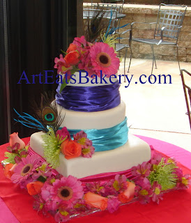 Three tier custom unique white fondant wedding cake design with purple, blue and pink silk wraps, peacock feathers and fresh flowers