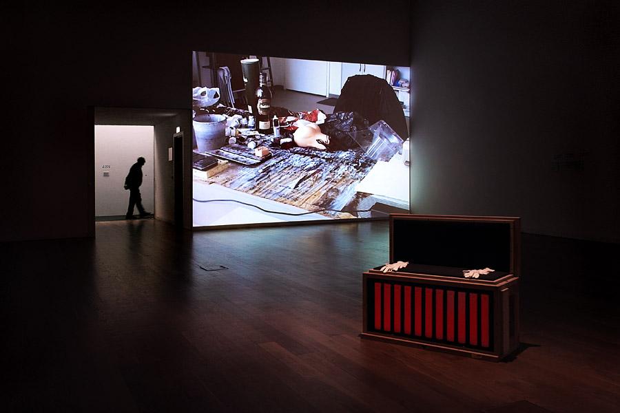 Fotografia a uma sala onde se passava uma projecção de diapositivos, zona que domina a imagem. Em primeiro lano uma arca com duas luvas em cima e à esquerda uma pessoa a passar. Na projecção, destaca-se uma cabeça de porco entre muitos objectos indistintos