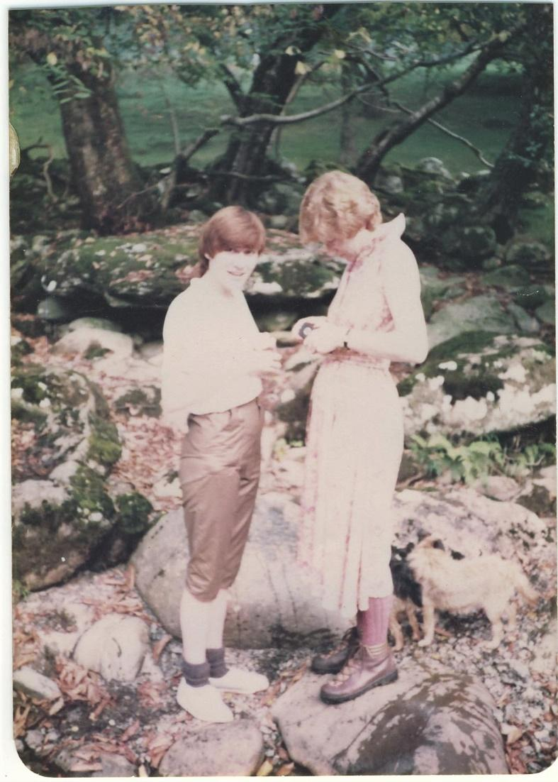 Sally and Gill in a photo from around 1980. Sally wears a white shirt and me-made capris, and Gill wears a dress. They're standing on a rocky outcrop with trees in the background.