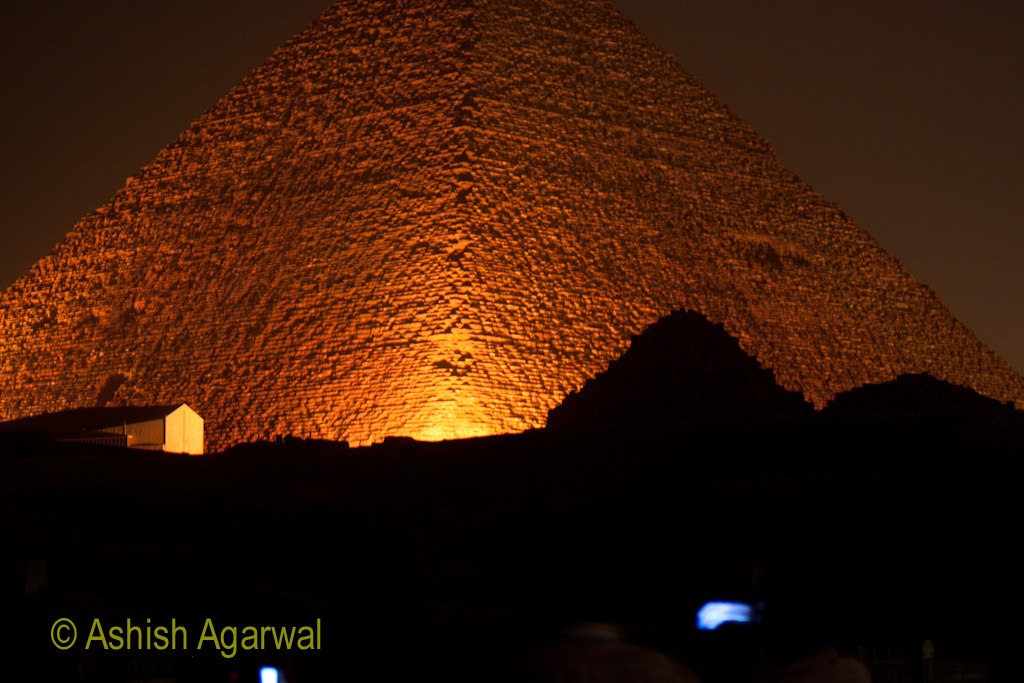 The Great Pyramid, bathed in orange light, during the sound and light show