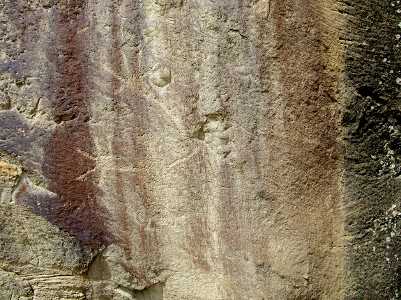 Mud-covered petroglyph with life-sized hands