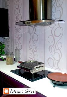 Parrilla portátil de mesa Vulcano Gres. Modelo acero inoxidable con canales plegadas recoge grasas. Presentación en cocina casera. Preparación de ascuas bajo la campana extractora.