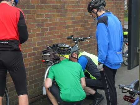 cyclists fixing bike chain