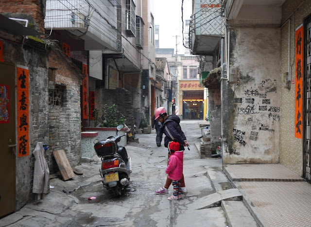 woman and little girl looking at a motorbike in an alley in Yangjiang, China