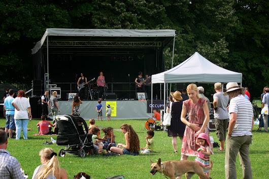 Bühne mit Rockmusikern, davor auf der Wiese hören zu: Frauen, Männer, Kinder und ein Hund.
