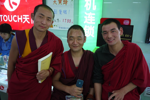 three Tibetan monks, one holding an iPhone, in Xining, Qinghai, China