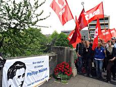 Demonstantinnen mit SDAJ- und DKP-Fahnen, Transparent mit Porträt Philipp Müller: »Hier starb vor 60 Jahren Philipp Müller, von der Polizei ermordet«.