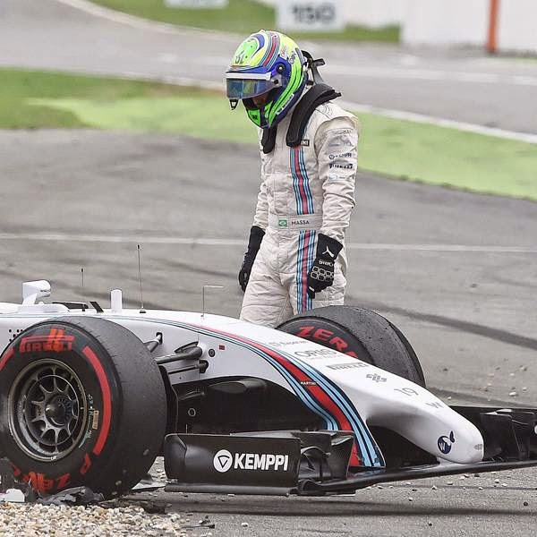 Williams?? Brazilian driver Felipe Massa stands next to his car after crashing during the German Formula One Grand Prix at the Hockenheimring racing circuit in Hockenheim, southern Germany, on July 20, 2014.
