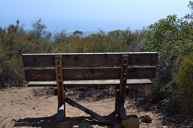 wooden bench by a rock memorial