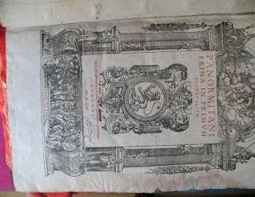 Portada arquitectónica del primer libro con texto en rojo y ¿emblema del gremio de impresores de Lyon?