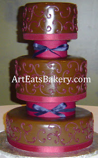 Custom unique modern chocolate brown fondant wedding cake with burgandy curlicues and blue, and burgandy ribbon separators