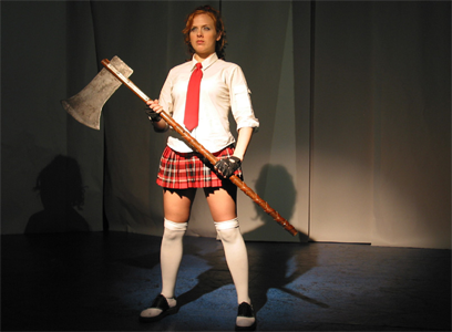 A young pale-skinned woman with golden-brown hair tied back in a ponytail stands on a stage holding a very large bladed axe with a long handle.  She is wearing anime-style school uniform - white blouse, red tie, short red tartan pleated skirted, white over-knee socks and flat shoes.