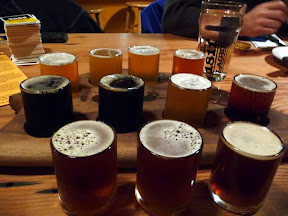Sampler at Fort George Brewing in Astoria. Back left to right: 1811 Lager, Quick Wit, Sunrise Oatmeal Pale Ale, Vortex IPA; Working Girl Porter, Cavatica Stout, Quiet Rye-It, Red Tide; OmegaTex, North 5, and Firkin Nut Red dry-hopped with Cascade Hops