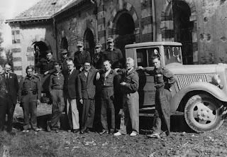 "A photograph of a group of men standing together outside in front of a car. The words ""Red Cross"" are visible on the door."