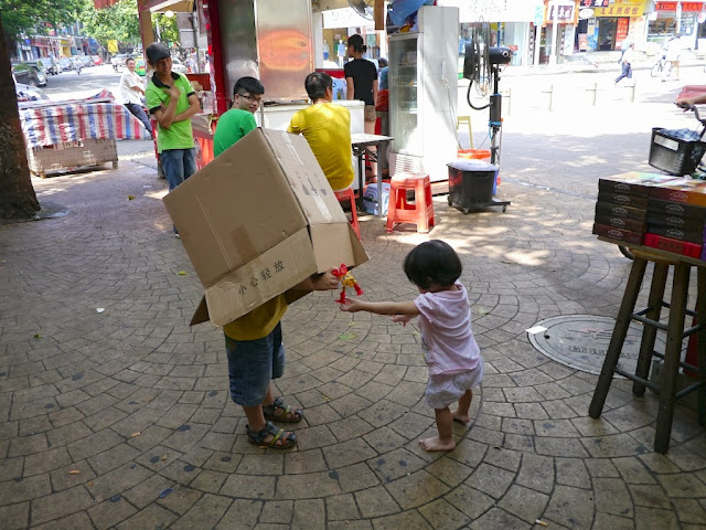 boy with a box over the top of his body and a barfeoot girl playing on a pedestrian street in Zhuhai, China