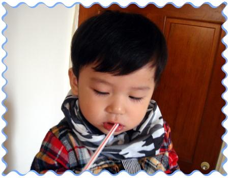 寶貝耕輔舔著吸管內殘留的奶茶