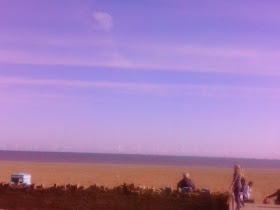 Cloudless corridor above windfarm at the seashore