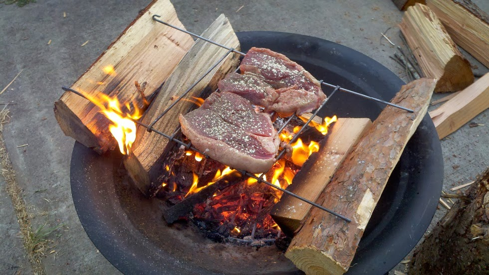 Cooking steak over a fire pit.
