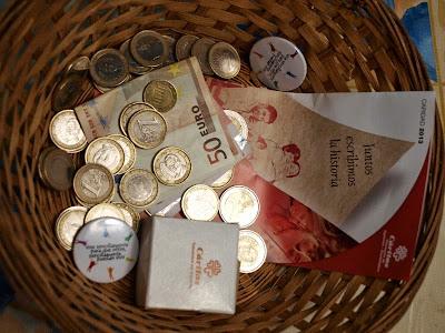 Cestillo de la colecta de Caritas, con pegatinas, donativos y dinero recaudado