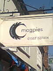 Magpies cream restaurant sign with stylised half moon of black magpie feathers