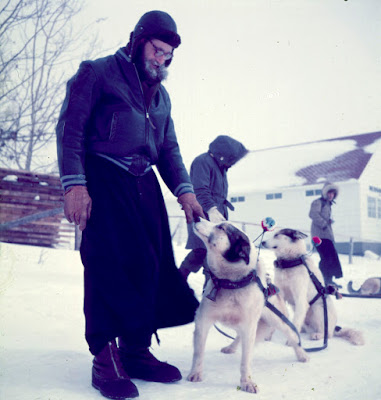 March 1955 La Loche (Father Mathieu and his dog team).  The Hudson's Bay Company store in the background built in the 1950's is still standing and is part of the  Northern Store.