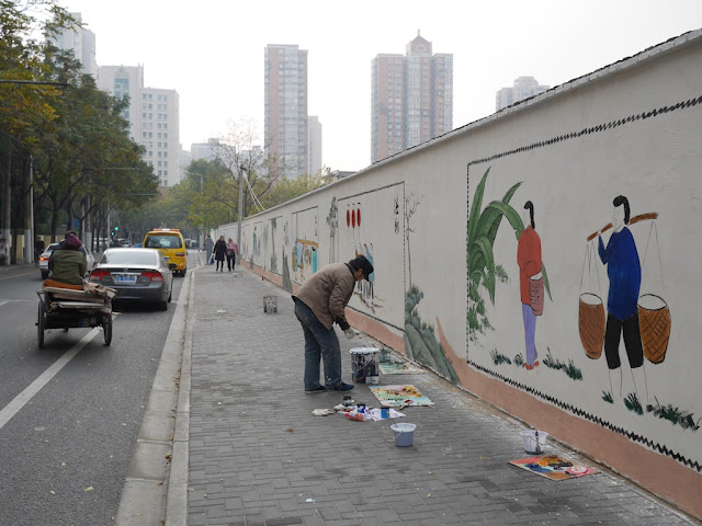 man painting traditional style scenes on a wall