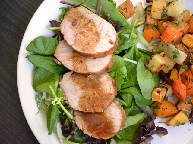 Four slices of Soy Dijon Pork Tenderloin on a bed of greens with a side dish on a plate