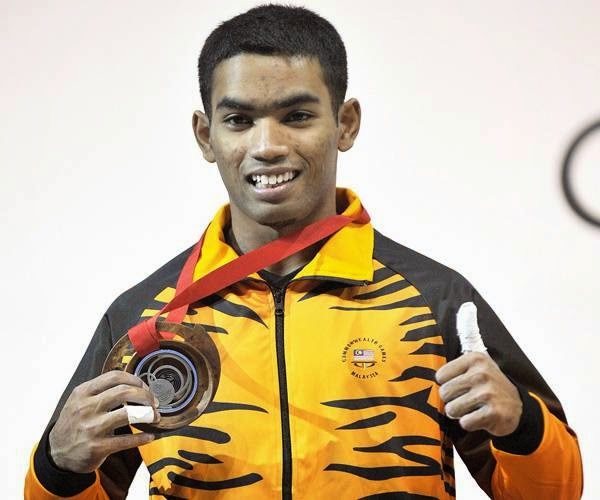 Malaysia's silver medalist Zulhelmi MD Pisol celebrates with his medal on the podium at the medal ceremony for the men's weightlifting 56kg class at the SECC Precinct during the 2014 Commonwealth Games in Glasgow, Scotland on July 24, 2014.